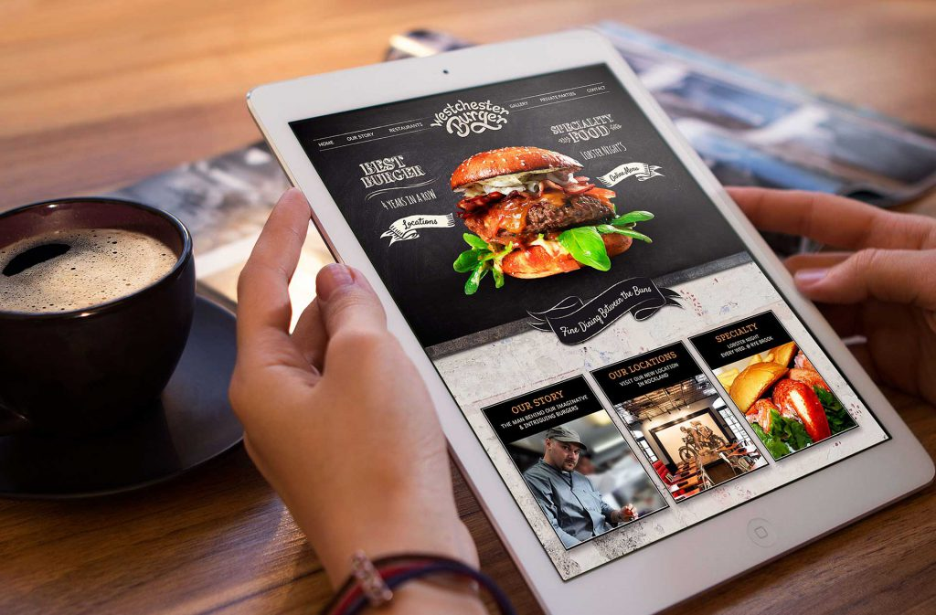 Burger restaurant website design in a tablet held by a person