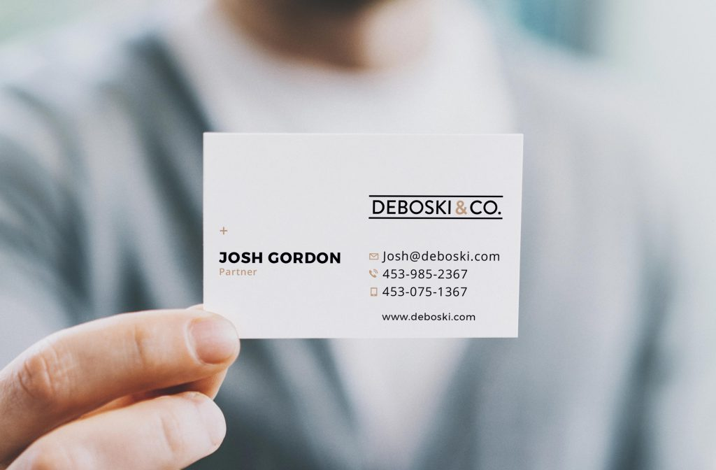 Deboski and Company small business business card design held by a business man