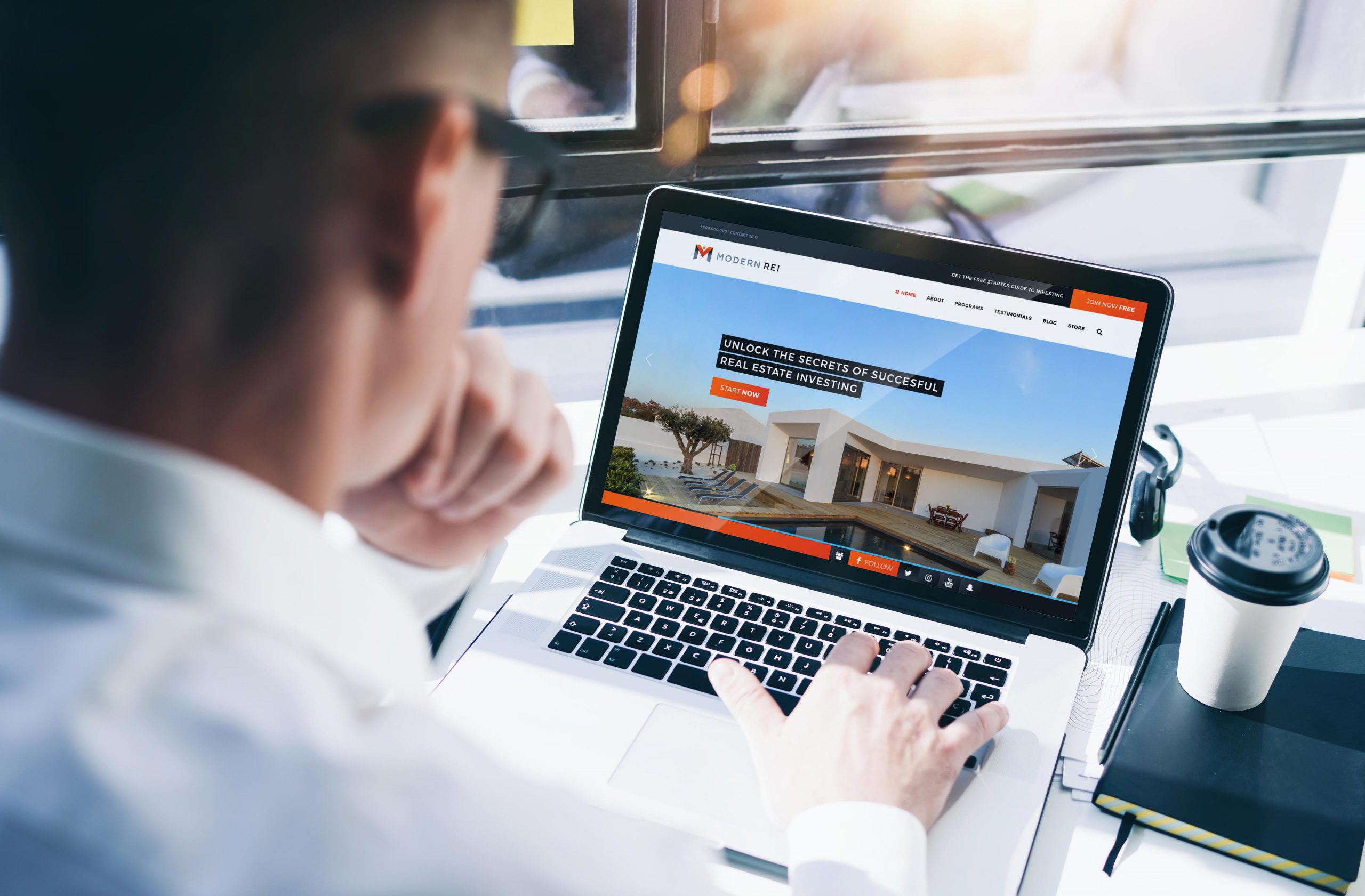 Business man viewing a real estate web design in a laptop